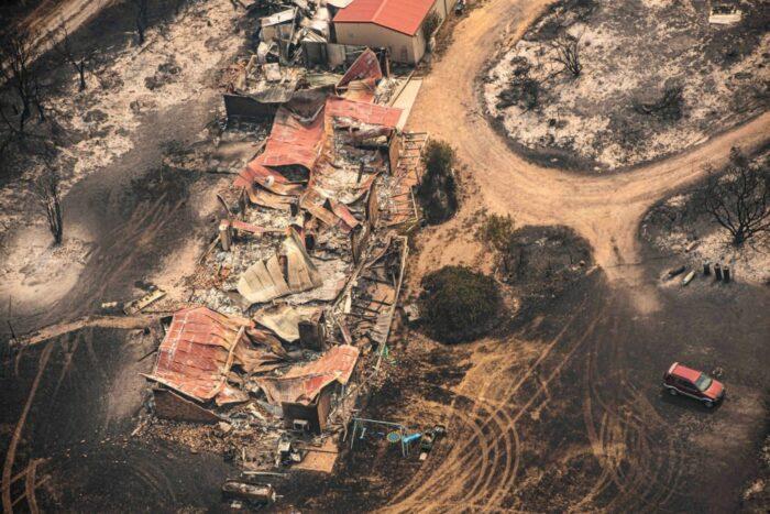 Verkohltes Geländer mit zerstörten Gebäuden