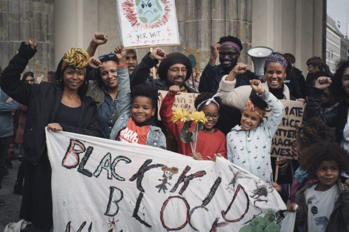 Erwachsene und Kinder heben die Black Power Faust vor einem Plakat mit der Aufsschrift Black Kids Block