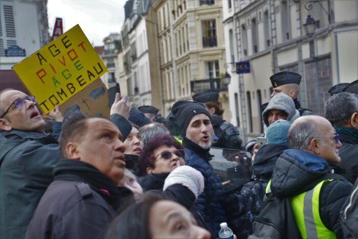 Mehrere demonstrierende auf der Straße, auf einem Plakat steht übersetzt »Scharnieralter ist Grabesalter«