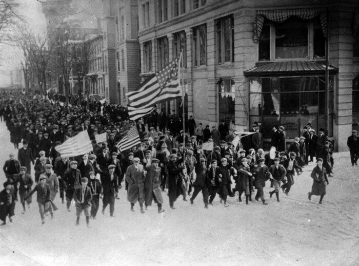 Demonstrierende marschieren auf der Straße mit amerikanischen Flaggen