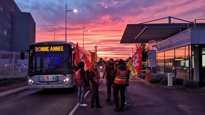 """Streikende am Eingang eines Betriebs. Ein bus fährt vorbei auf dem steht """"frohes neues Jahr"""""""
