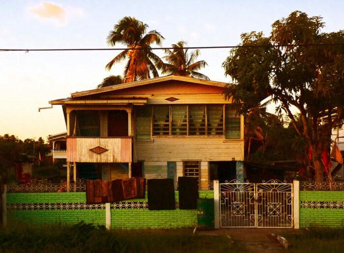 Frontansicht eines Hauses mit Holz-Fassade vor Palmen