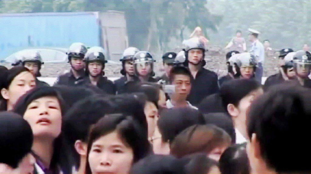 Streikende chinesische Arbeiterinnen vor einer Polizeikette