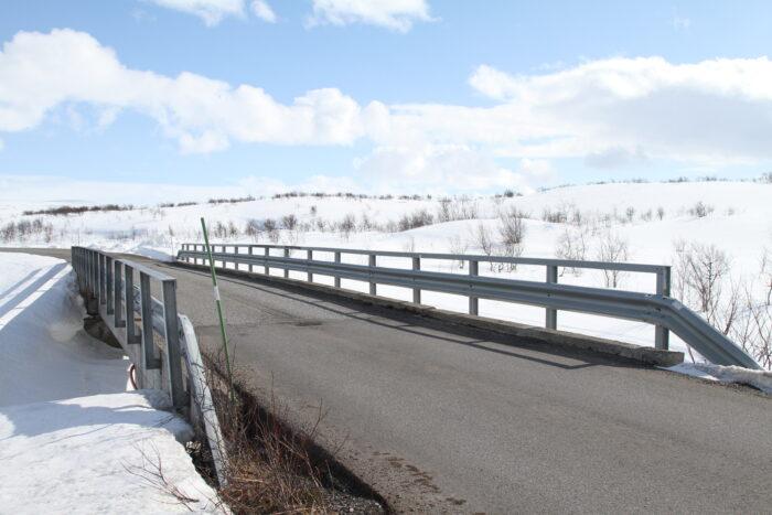 Brücke führt über einen Fluss auf einer schneebedeckten Landschaft