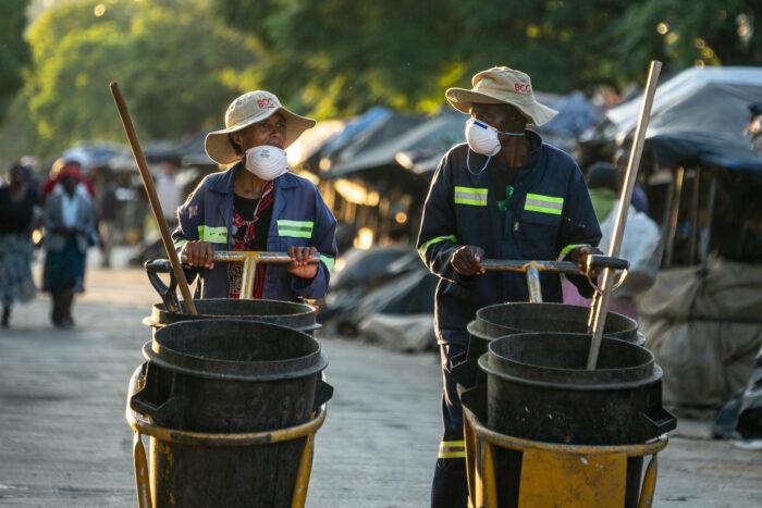 Zwei Mitarbeiter der Stadtreinigung laufen über leere Stände eines Marktes