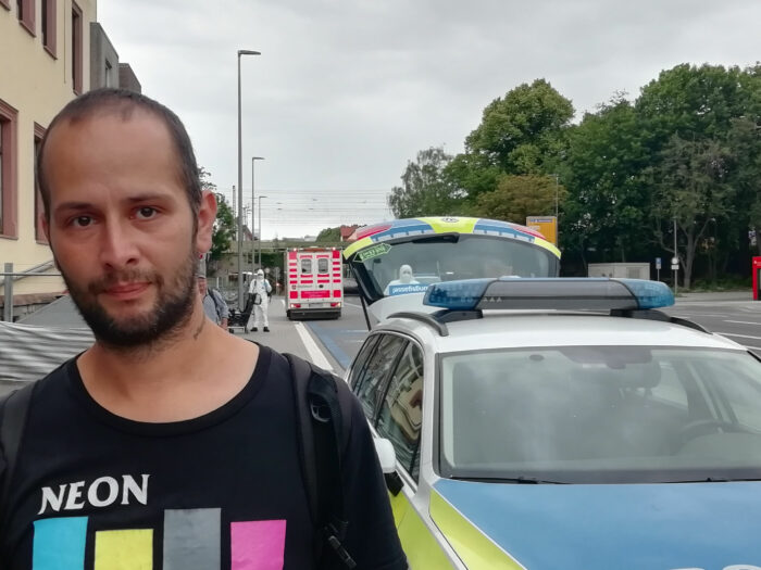 Mann vor einem Polizeiauto und einem Krankenwagen an einer Straße