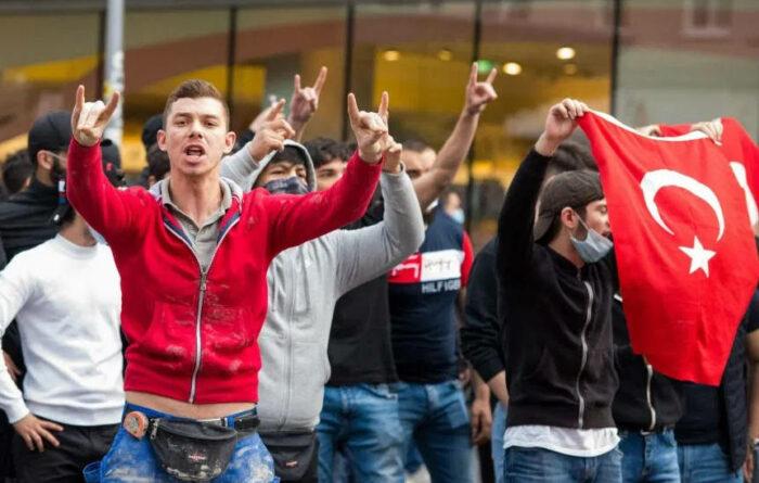 Junge Männer zeigen den Wolfsgruss und andere schwingen türkische Flaggen