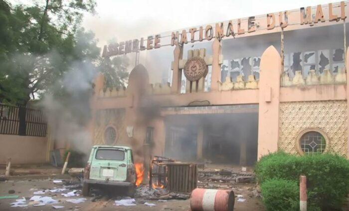 Eingang zum Parlamentsgebäude mit den Lettern Assemblee Nationale du Mali, die Lettern und die Glasfront sind beschädigt. Davor ein brennendes Auto und lose Blätter