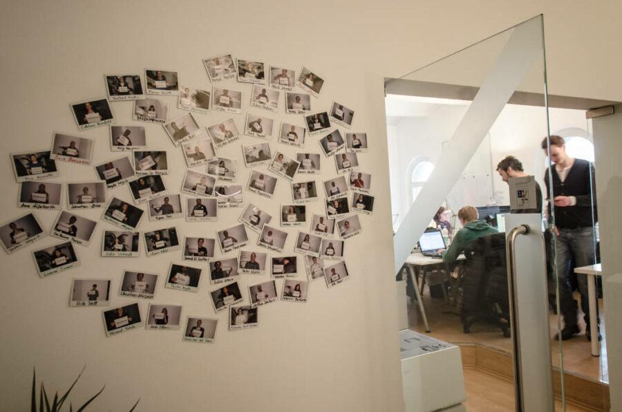 Fotowand von Mitarbeiter:innen neben einem Büro mit Beschäftigten