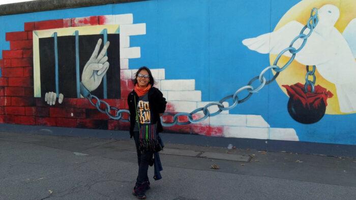Zara Alvarez lächelnd vor der Berliner Mauer
