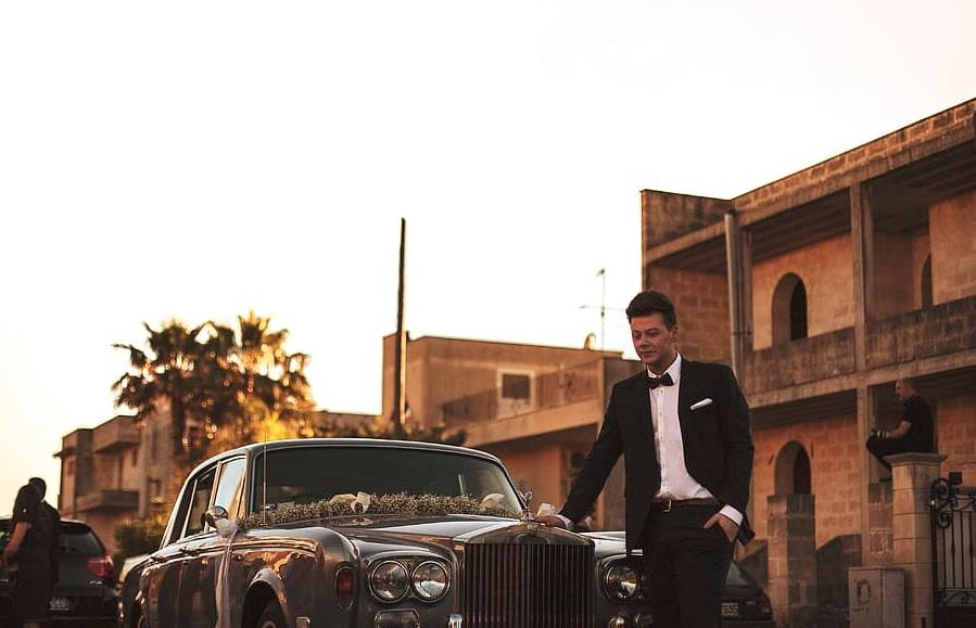 Mann im Anzug vor einem Luxusauto