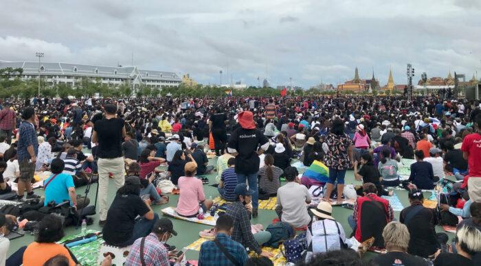 Tausende Menschen sitzen auf einem weiten Platz