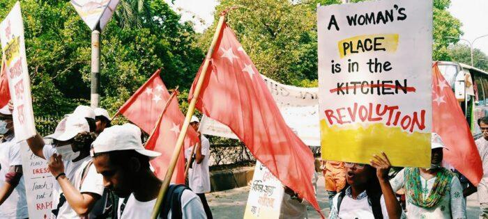 """Demonstrantinnen und Demonstranten mit Flaggen, auf einem Plakat steht """"A Woman's place is in the Kitchen"""", kitchen ist durchgestrichen und stattdessen steht revolution"""