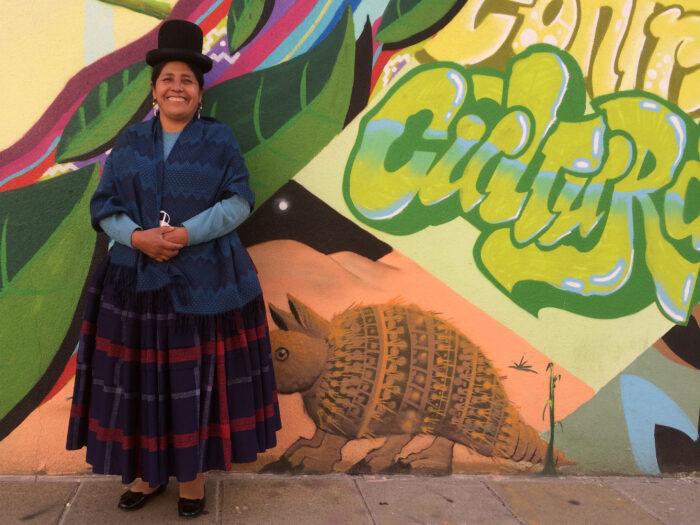 Francisca Alvarado Mamani vor einer bunten Graffitiwand