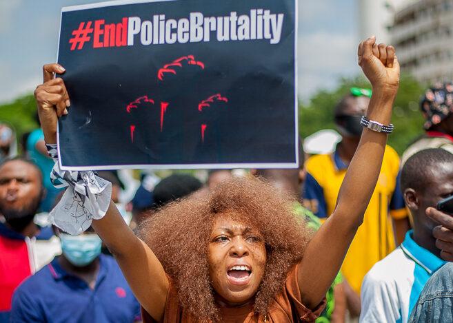 """Eine Frau hält bei einer Demonstration ein Schild hoch, auf dem """"End Police Brutality"""" steht und hebt die Faust"""