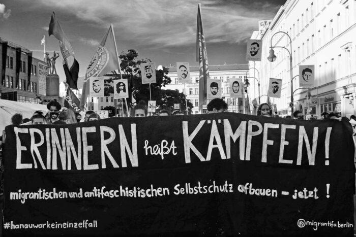 """Aktivistinnen und Aktivisten hinter mit Bildern der Opfer von Hauanu und einem Plakat mit der Aufschrift """"Erinnern heißt kämpfen – migrantischer und antifaschistischer Selbstschutz aufbauen – jetzt"""""""