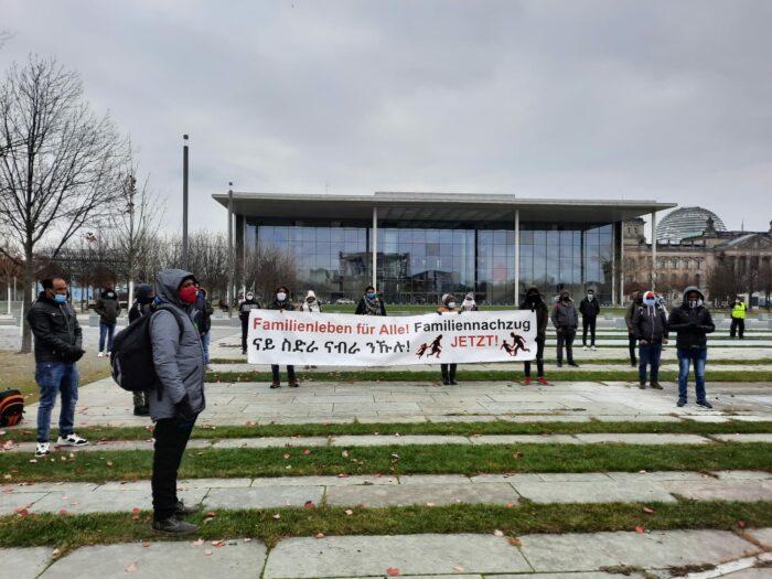 Demonstrationsteilnehmer:innen stehen mit Abstand vor dem Bundeskanzler:innenamt