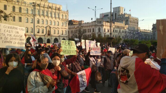 Eine Menschenmenge hält Plakate hoch, vereinzelte tragen die Peruvianische Flage als Umhang