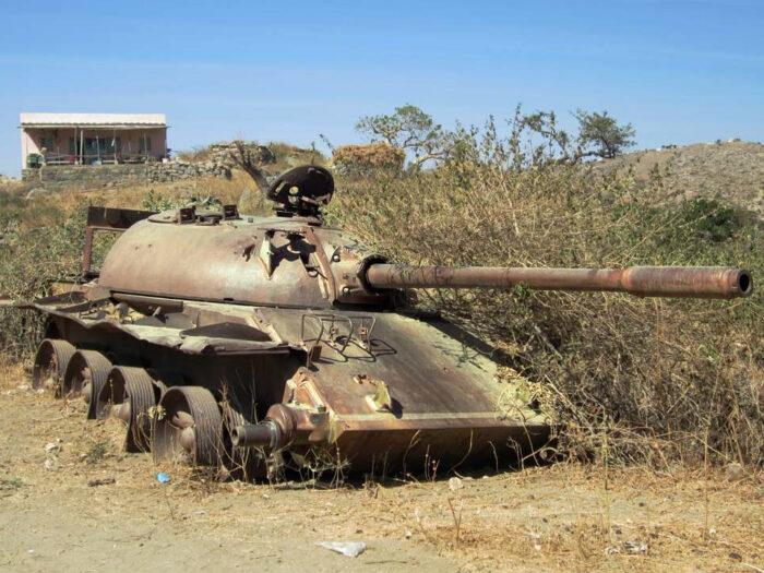 alter rostender Panzer am wegesrand, teilweise von Büschen zugewachsen