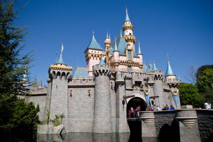 Das Disneyschloss mit spitzen Türmen, einem Schutzwall und einem Graben, über die eine Brücke zum Eingang führt