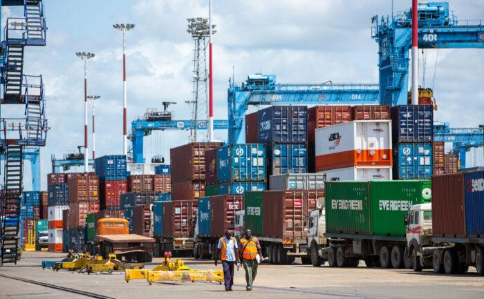 Container und Kräne, zwei Arbeiter laufen im Vordergrund
