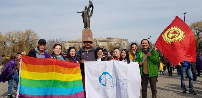 Aktivist:innen posieren mit Krigisischer und LGBT-Flagge vor einer Statue