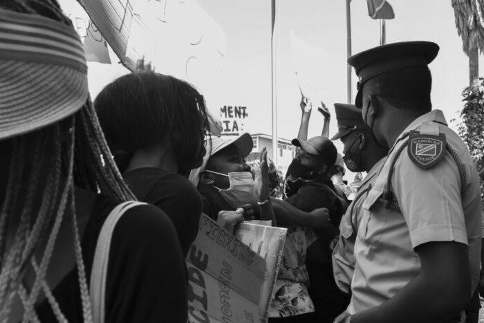 Protestierende skandieren vor zwei Polizisten