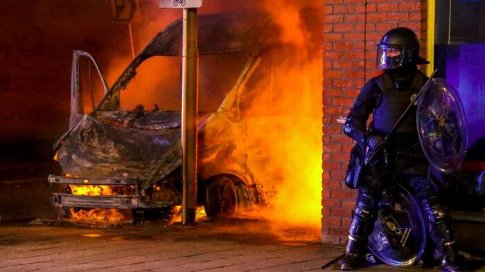 Brennender Lieferwagen, daneben ein hochgerüsteter Polizist mit Schild und Schlagstock