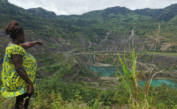 Eine Frau steht am Rande eines Kraters und zeigt auf edssen Mittelpunkt, eine vom Berbau geformte Landschaft