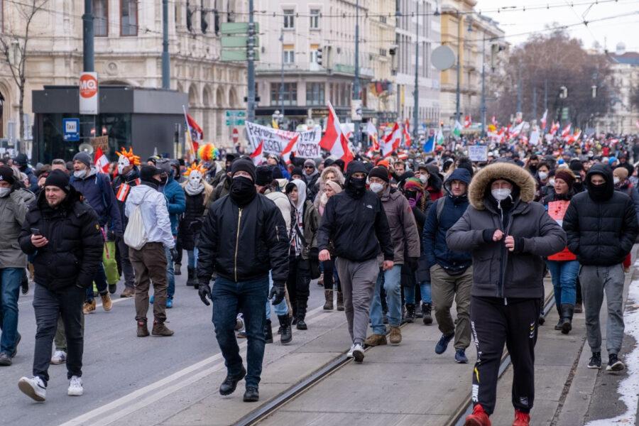 Eine Demonstration mit vielen Österreich-Flaggen. Im Vordergrund bedrohlich aussehende, maskierte Männer