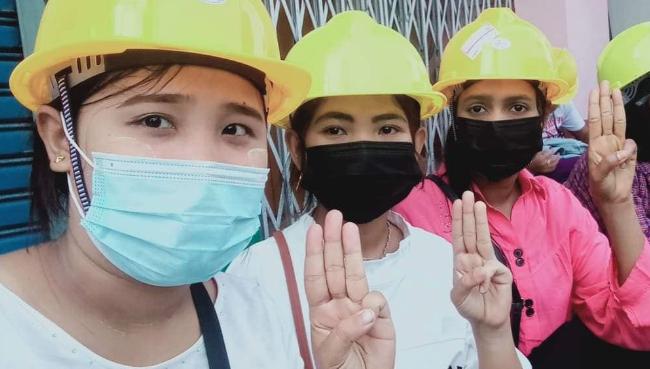 Drei Arbeiter:innen halten drei Finger hoch