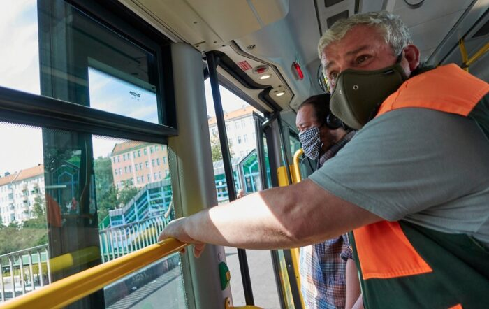 Zwei Personen mit Masken in einem Bus.