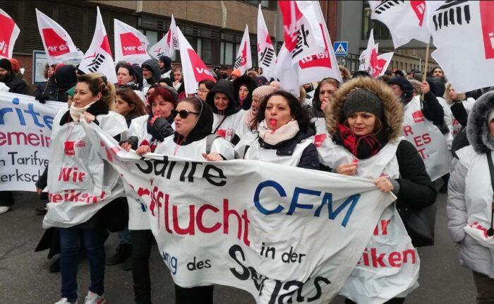 Arbeiterinnen mit ver.di-Westen, Fahnen, Trillerpfeifen und Banner.