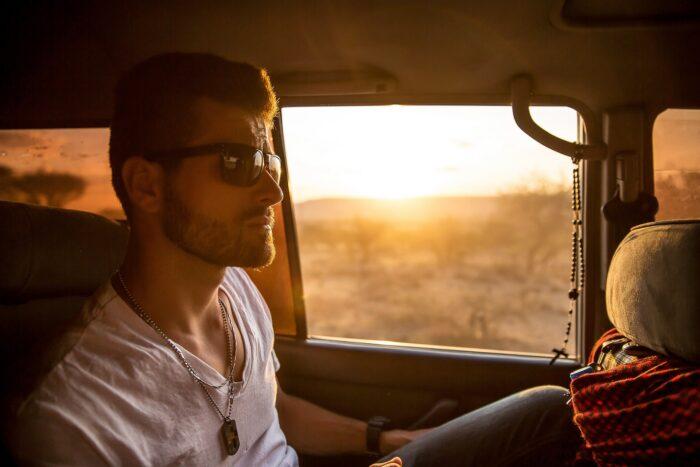 Weißer Mann mit Sonnenbrille blickt cool in einem Jeep vor einer Savannenlandschaft drein