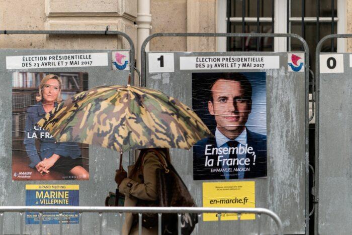 Eine Person mit Regenschirm geht an einer Wand vorbei, an der zwei Plakate hängen, eines mit Macron und eines mit Le Pen.