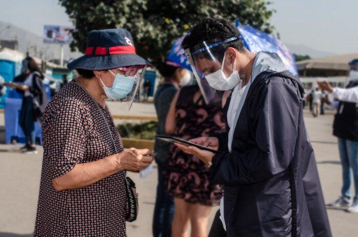 Eine etwa ältere Frau und ein jüngerer Mann, beide mit Masken und Schutzvisieren, schauen auf eine Wählerliste.