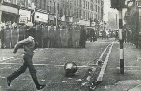 Ein Junge überquert eine Straße. Im Hintergrund ein versteckt sich die Polizei in reihe hinter ihren Schildern
