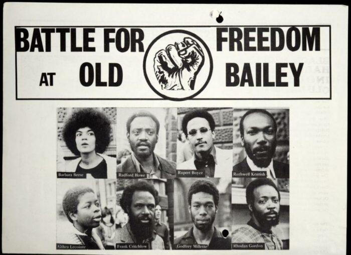 """Ein Plakat mit neun Portraits und deren Namen, oben ein Aufruf """"Kampf für Freiheit beim zentralen Strafgericht"""", in der Mitte eine Faust"""