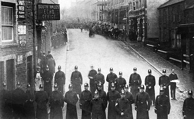 Schwarzweißbild zeigt eine Polizeikette und eine sich im Anmarsch befindende Menschenmasse.
