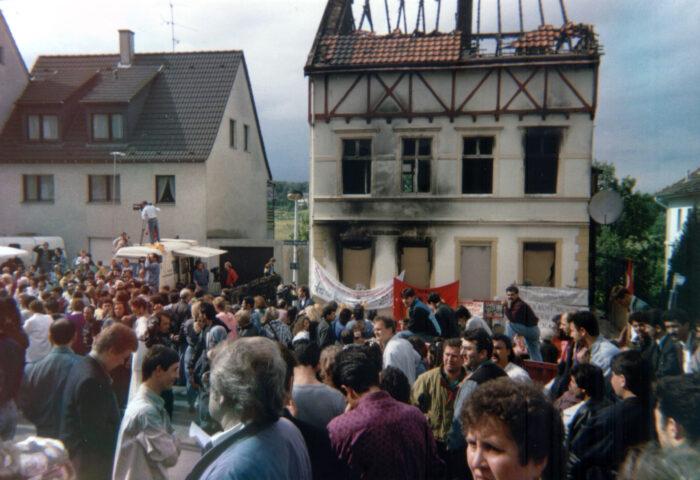 Eine Menschenmenge steht vor dem von Nazis abgebrannten Haus in Solingen.