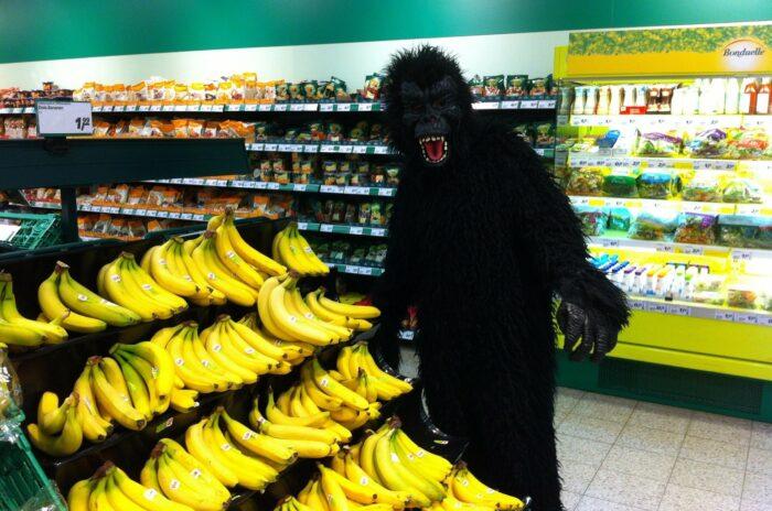 Ein Mensch im Gorilla-Kostüm beim Bananen kaufen