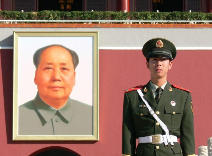 Portrait von Mao, daneben ein Soldat in Haltung