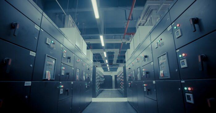 Bild von schwarzen Schränken mit Signallichtern in einer großen, überdachten Lagerhalle. Die Schaltschränke gehören zu einem Daten-Zentrum