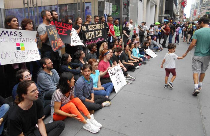 Demonstrantinnen und Demonstranten stehen und Sitzen vor einem Gebäude. Sie halten Schilder in der Hand, die die Zusammenarbeit von Microsoft und der Zollbehörde ICE verurteilen