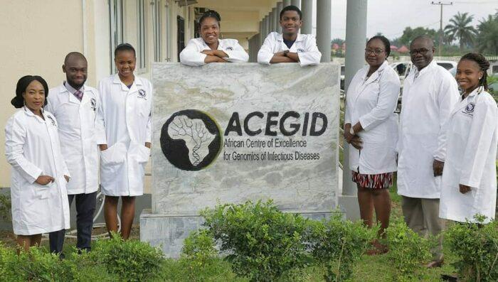 """Ein Team von Forscher_innen im Familienfoto um eine Infotafel mit der Aufschrift """"ACEGID, African Centre of Excellence for Genomics of Infectious Diseases"""""""
