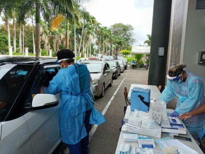 Ein Drive-in mit einer Schlange von Autos. Vorne verabreicht eine Frau den Autofahrer:innen Impfungen